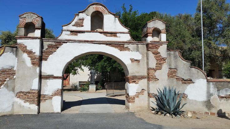 Mission San Miguel Arcángel, San Miguel, California - The 16th of 21 Spanish missions founded in 1797. This is entrance to courtyard with Father Serra statue and museum. Come in Spring to see all the blooming cactus and flowers and stop at the cemetery next door where many Native Americans are buried. #Blue #StunningStructures