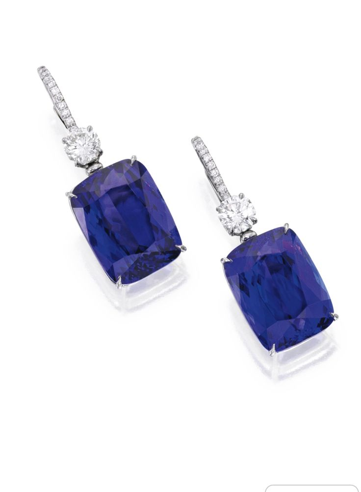 Pair of Platinum, 18 Karat White Gold, Tanzanite and Diamond Earrings. Suspending two cushion-cut tanzanites weighing approximately 33.15 carats, accented by two modified octagonal brilliant-cut diamonds weighing approximately 1.50 carats, the tops further set with small round diamonds.