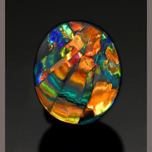 """Fine Black Opal with Pattern—""""The Cathedral Window"""" Lightning Ridge, Australia With the pattern reminiscent of the rays of sun coming through a cathedral stained glass window, this fine opal displays predominantly red flash, with orange, yellow, green and blue large """"flagstone"""" pattern intermingled, with black potch to the reverse."""
