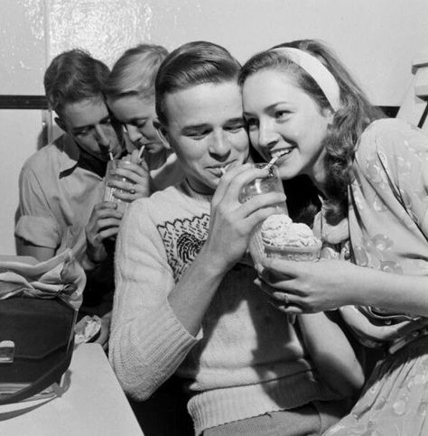 1950's: A group of teenagers enjoy sharing laughs, memories and milkshakes while on a double date.