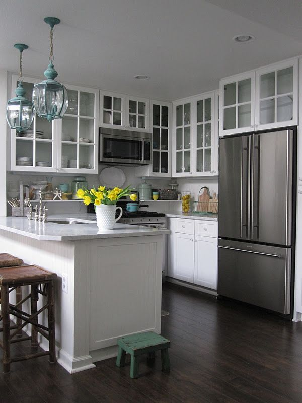 honed carrera marble counters, all white, pops of turquoise/green. wood floors, mother of pearl backsplash!