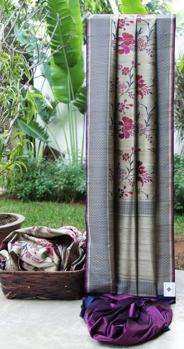 This tan coloured Benares tussar has a floral pattern in purple, red and navy blue. The border is in navy blue, purple and tan. The pallu is in tan and navy blue giving it a distinguishing finish