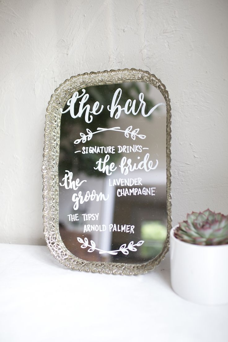 Signature drink sign, hand painted for wedding on antique vanity mirror. His and hers cocktails. Floral garlands.