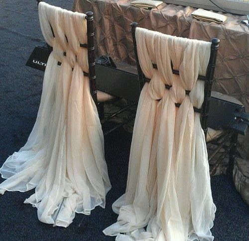 beautiful romantic elegant chair covers for a wedding | bride and groom chair covers | yards of silk fabric interweaved with the chiavari chairs | flowing sheer silk fabric in ivory flowing on the floor like a wedding gown dress