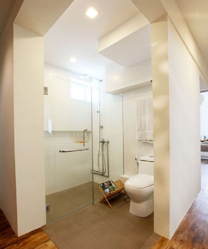 spacious semi detached open plan bathroom, with thick white walls, containing large glass shower cabin, modern oval toilet seat, brown carpet and wooden floor