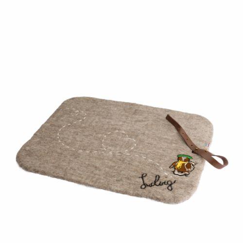 Her sitter du mykt og varmtStørrelse: 35x45cm.Laget av 100% merinoull, med håndbrodert signatur og dekorsøm. Vevd merke av Solan, Ludvig og Soline.Sitteunderlaget er tovet som et helt stykke. Det bevarer ullens vannavstøtende egenskaper og holder deg varm og tørr, selv på fuktig underlag.Har en praktisk skinnreim, slik at det enkelt kan rulles sammen og puttes i tursekken.Ludvig i naturbrun farge, Solan i grå og Soline i rosa.