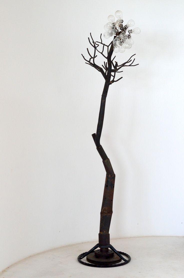 Árvore do Sertão. Descrição: cabideiro para roupas em forma de árvore do sertão, representando os seus galhos secos e as flores recém-nascidas após as primeiras gotas de chuva no sertão.  Técnica: haste feita de pedaços de tubos sucateados, galhos de pedaços de ferro redondo, base de volante e disco de freio, flores de lâmpadas incandescentes queimadas e pintura em verniz fosco.  Peso: 5 kg Dimensão: 200 x 48 cm