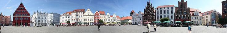 """The market in Greifswald, Mecklenburg, one of the old towns usually built around one/several market places with a church/town hall...characterised by a """"Hanseatic"""" style also found in parts of northern Germany, as well as in countries bordering the Baltic Sea like Estonia or Latvia. Distinctive feature of towns in Mecklenburg and Vorpommern are Gothic red brick churches dating back to the Middle Ages. Towns were founded at the Baltic Sea, around a lake or a river for logistical/trade…"""