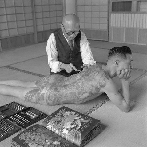1946, Tokyo, Japan ~ A Japanese tattoo artist works on the shoulder of a Yakuza gang member. ~ Image by © Horace Bristol