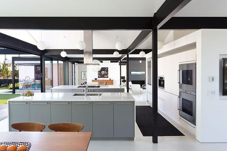 At a sleek contemporary home for sale in California, the industrial-chic kitchen opens up to a formal dining area