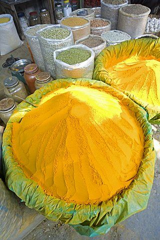 Spice market stall with large bowls of turmeric powder in early morning market on the banks of the Brahmaputra river, Guwahati, Assam, India, Asia