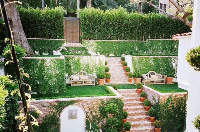 Brick stairs run through the tiered garden and lead to double carved garden doors!