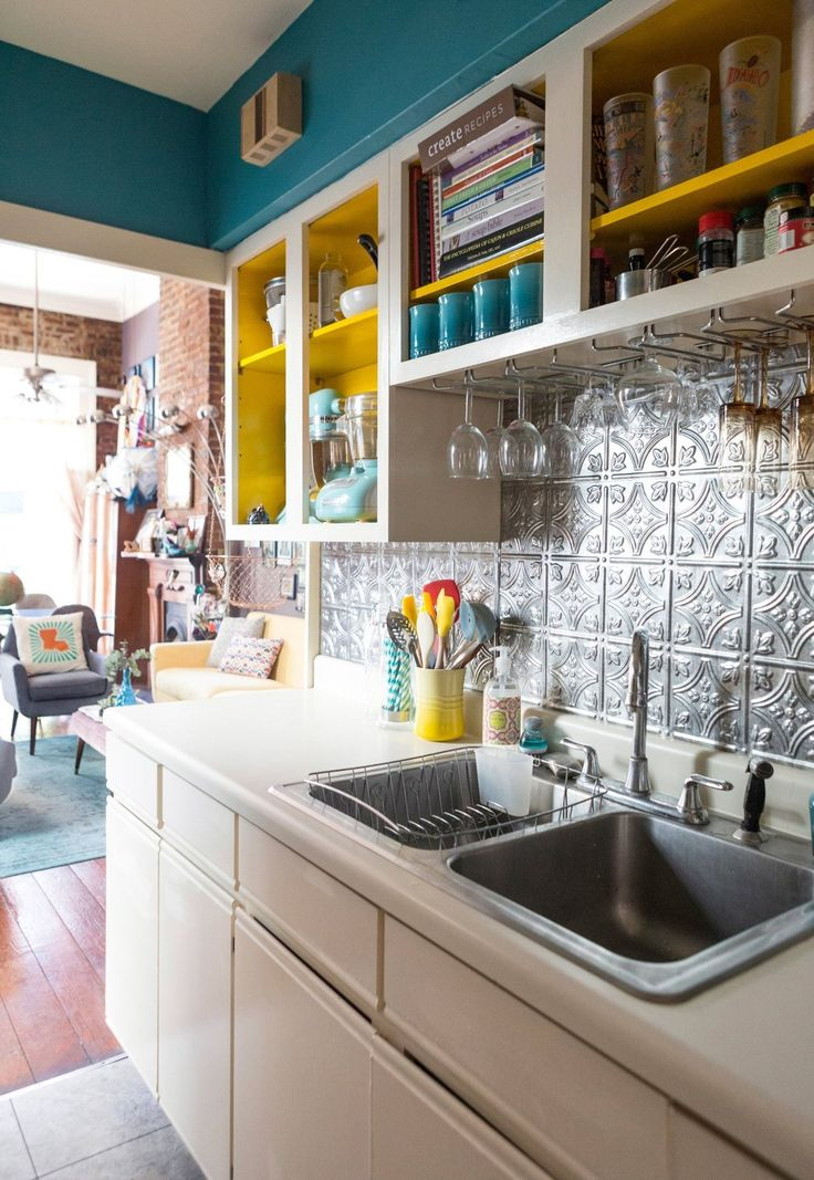 Bright painted cabinets and tin ceiling style backsplash from Kerry's Fun French Quarter Apartment