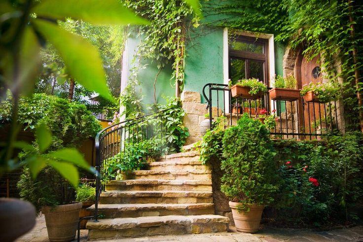 Zwei große Tontöpfe entspannen am Fuße der Treppe, während hängende Pflanzgefäße wachsen die Pflanzen auf den oberen Metall Geländer. Keine zusätzlichen blühenden Pflanzen nur einige Blumen sind sichtbar, während Reben und grüne Büsche wachsen reichlich rund.