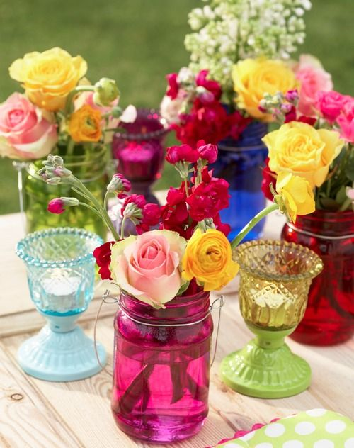 Spring entertaining. Colored glass and vibrant flowers.