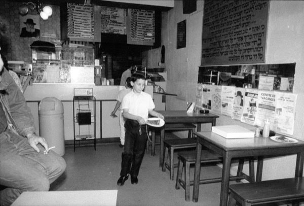 An Orthodox Jewish boy getting a slice of pizza in a kosher pizza shop in France.