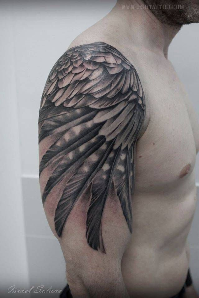 Black and grey wing tattoo on the right upper arm and shoulder.