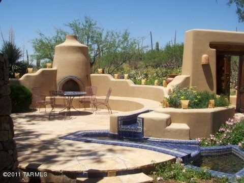 An enclosed Southwest design style patio with outdoor fireplace and shelf seating attached to Southwest color stucco walls.