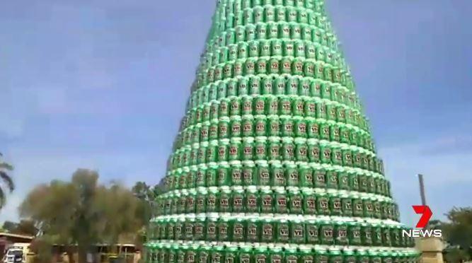 Man maakt kerstboom uit bierblikjes