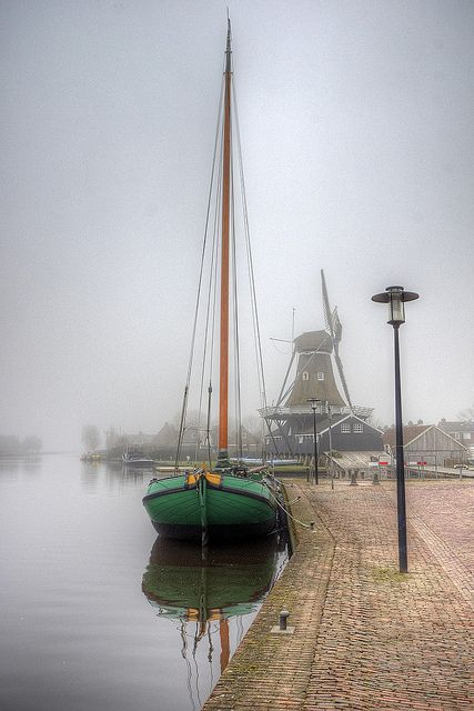 Woudsend, The Netherlands; Boat and windmill on a misty day