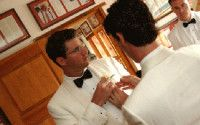 Groom's Best Man fixing his boutonniere. Photo by Tomas Ramos.