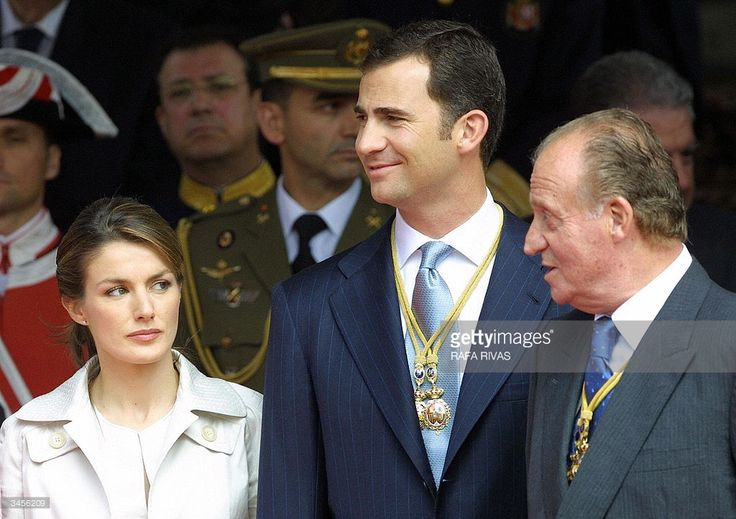 Prince Felipe (C) smiles as his father, Spain's King Juan Carlos I (R) talks to Prince Felipe's fiancee Letizia Ortiz (L), 22 April 2004 in the Spanish city of Madrid, during a military parade to celebrate the opening of the Spanish Parliament's eight legislature. Expressing 'hope and optimism' for his country's future, King Juan Carlos formally opened the new Spanish parliament Thursday following March 14 elections which saw a Socialist, Jose Luis Rodriguez Zapatero, promise a new direction…