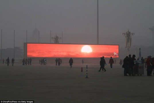A ChinaFotoPress photographer visiting Beijing snapped up this image of a fake sunrise displayed on a large outdoor screen amidst a dense cloud of smog graying out the horizon and even a nearby building.  Read more: Is Beijing's Pollution So Bad that Residents Need a Fake Sun?
