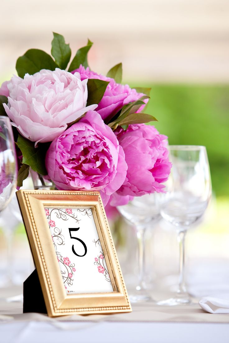 Pink peony wedding centerpieces with gold frame table numbers.