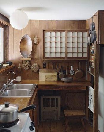 まるでタイムスリップしたような気持ちになるのは、現代的アイテムとヴィンテージアイテムの絶妙なミックス具合から。格子の戸棚や壁に直接ディスプレイするキッチン用品がポイントに。