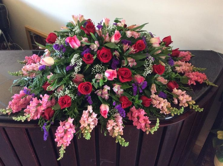 A full Casket spray for a woman in all pink, purple and burgundy coloured flowers. The snap dragons and babies breath add a very interesting texture to this funeral armament.