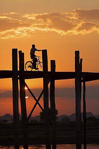 Cyclist on the U Bein teak bridge at sunset, Amarapura, Mandalay, Myanmar…