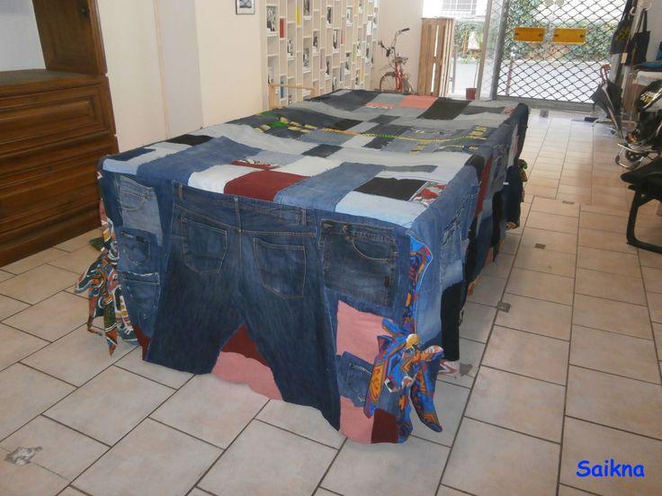 J'ai réutilisé une vingtaine de pantalons en jeans aussi différents les uns que les autres, des chutes de tissus africains ainsi que du tissu en coton, pour les 4 coins. Saikna créations J'ai réalisé un patchwork avec les jeans créant ainsi l'originalité de cette oeuvre. Elle comporte 45 poches de tailles diverses et variées. Elle mesure 4 mètres sur 2,86 mètres.