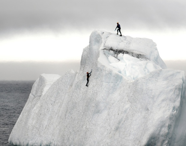 On a Wednesday (April 18, 2012) afternoon in St. John's, N.L., Justin Emberley saw a 45-metre iceberg floating less than 100 feet from shore in Quidi Vidi Harbour. He and a friend (a Ph.D. student studying glacier modeling) put on their wetsuits and life vests, threw their ice picks and clamp-ons in their bags, jumped in the frigid ocean and swam to the iceberg. Both men are avid rock climbers so climbing the ice was not too difficult.