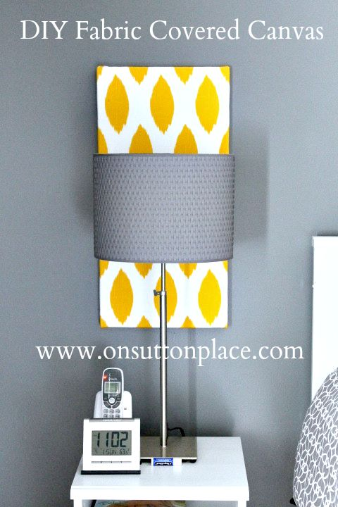 A fabric covered canvas adds a pop of color over a bedside table and is the perfect size.