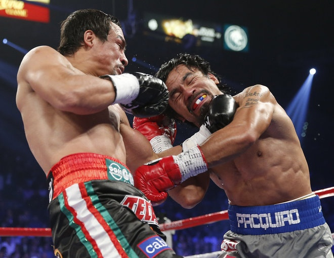 Juan Manuel Marquez, from Mexico, left, and Manny Pacquiao, from the Philippines, trade blows during their WBO world welterweight fight Sunday, Dec. 9, 2012, in Las Vegas. Eric Jamison / AP
