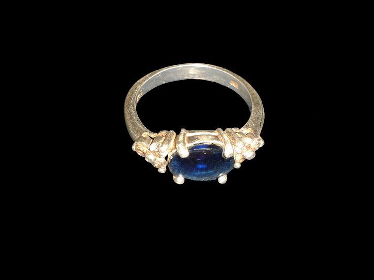 Hermoso anillo en plata 925 con piedra azul central y tres piedras brillantes más pequeñas,
