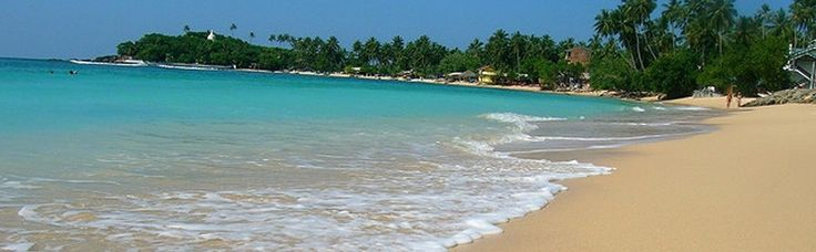 Unawatuna is fringed with swaying green palms facing a clear blue bay protected by beautiful coral reefs