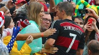 Bastian Schweinsteiger of Germany celebrates with Sarah Brandner. (And who's that creepy dude photobombing in the middle?)