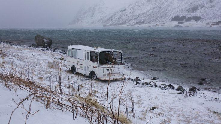 En parkert turbuss er kastet flere meter av parkeringsplassen ned i fjæra i Skjeldfjord i Flakstad k - En parkert turbuss er kastet flere meter av parkeringsplassen ned i fjæra i Skjeldfjord i Flakstad. - Foto: Tommy Johansen /