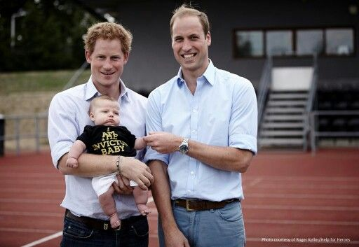 LIE: Prince William and Prince Harry with baby George TRUTH: This is not Prince George. This photo was taken at the Invictus Games where Harry and William were greeting athletes, one of whom brought his child in an Invictus Games t shirt.