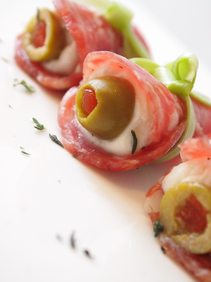 Bocconcini Olive Salami Canapes: Press pimento-stuffed green olives into mozzarella balls; roll in pieces of cured salami; secure & tie with chive strands. Serve on a platter & garnish with fresh thyme.: