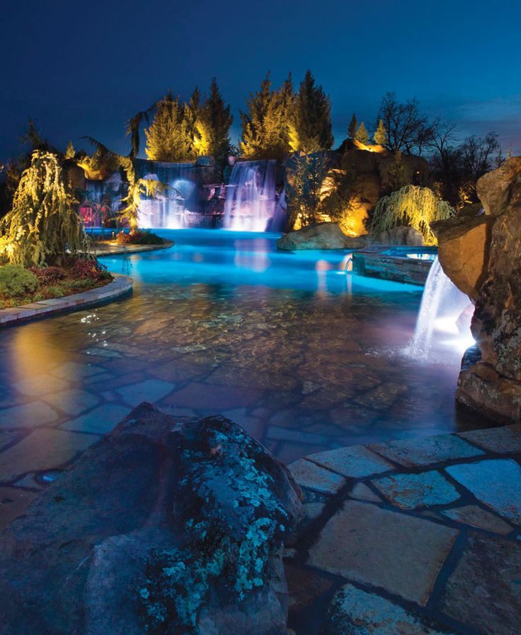 Amazing beach-entry pool at night with tall rock waterfalls and color-changing LED lighting. Pool by Caviness Landscape Design, Inc., Edmond, OK http://www.luxurypools.com/swimmingpoolbuilder/Caviness-Landscape-Design-Inc?fid=147  Photography by K.O. Rinearson