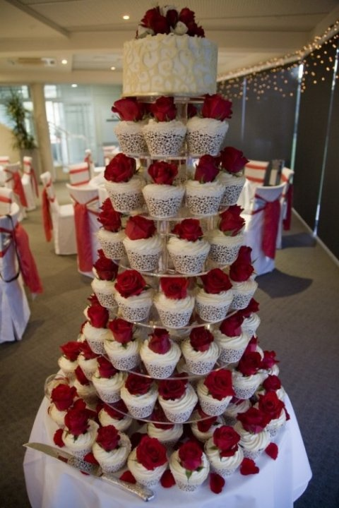 <3 cuppies with a cake on top for the bride and groom