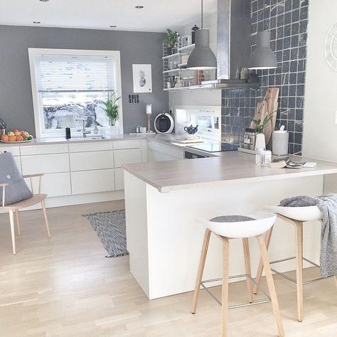 Eine schicke und moderne küche die kombination aus grau und weiß wirkt sehr freundlich tolle lampne designer stühle und schicke fliesen machen diese