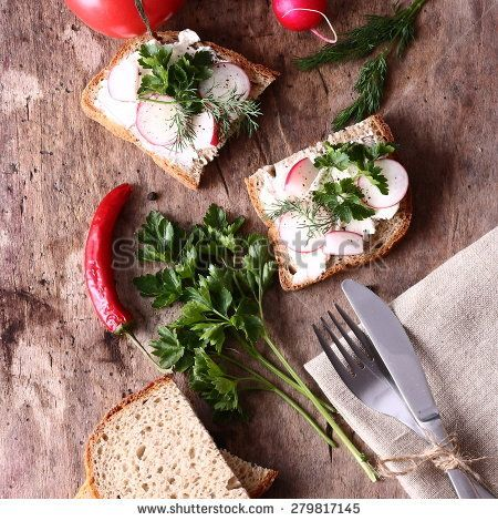Sandwiches with fresh vegetables and cream cheese on a table