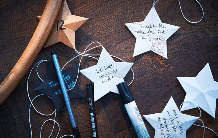 Stylos et étoiles en papier avec messages écrits, posés sur une table.