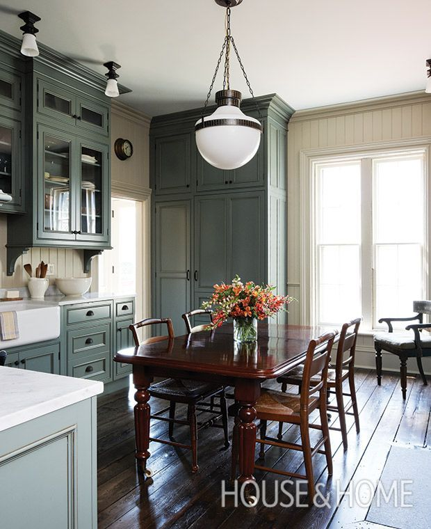 A historical hue — Farrow & Ball's Green Smoke (47) — and classic country style give the cabinets in this Halifax kitchen a distinctly furniture-like feel, a look that's bolstered by decorative brackets and ample crown moldings. Photo:  Janet Kimber  Design:  Kenneth McRobbie and Colin Blanchard