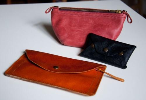 Pomarańczowy portfel, kosmetyczka w kolorze łososiowym i czarny wizytownik.