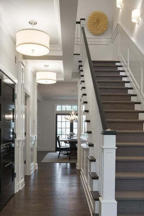 Chic, long foyer features a glossy black paneled closet door facing a staircase illuminated by white drum pendants with ribbon trim.