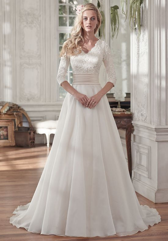 Demure and sophisticated, this elegant A-line wedding dress offers a gorgeous lace bodice, pleated Romance satin belt at the waist, and soft Vicenza organza skirt. Three-quarter sleeves lend a demure alternative to a bare shoulder. Finished with V-neckline and covered buttons over zipper and inner elastic closure.